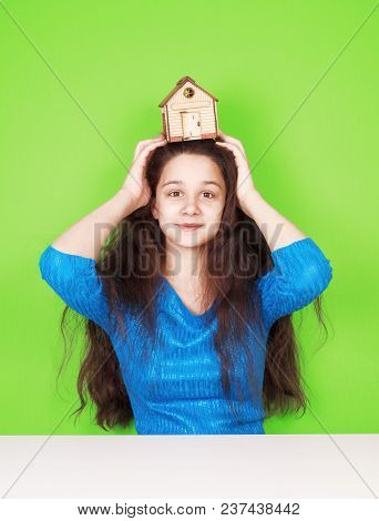 Charming Young Woman With A Model Of A Wooden House On Her Head. The Green Background