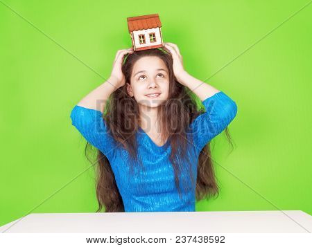 Charming Young Woman With A Model Of A Wooden House On Her Head. She Looks Up. The Green Background