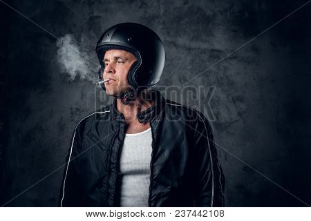 Middle Age Male In Motorcycle Helmet And Leather Jacket Smoking A Cigarette On Grey Background.