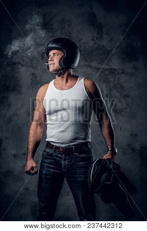 Middle Age Biker Smoking A Cigarette On Grey Background In Photo Studio.