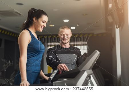 Fitness instructor helps young woman on elliptical trainer. Cardio workout in gym, healthy lifestyle, copy space poster