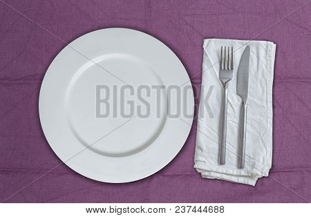 Empty Plate And Cutlery On Violet Cloth.