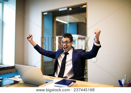 Happy Smiling Man Winner With Arms Raised Rejoices In Its Business Victories Watching On Laptop Comp