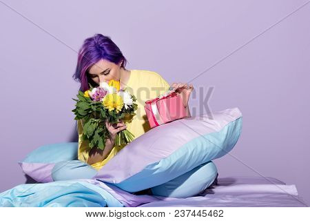 Beautiful Young Woman With Gift Box And Flowers Sitting In Bed