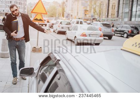 Bearded Businessman With Coffee Cup Catching A Taxi. He Does Not Have Time, He Is Going To Talk On T