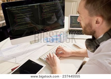Busy Software Developer Sitting At Desktop Computer And Typing On Keyboard While Setting Up Computer