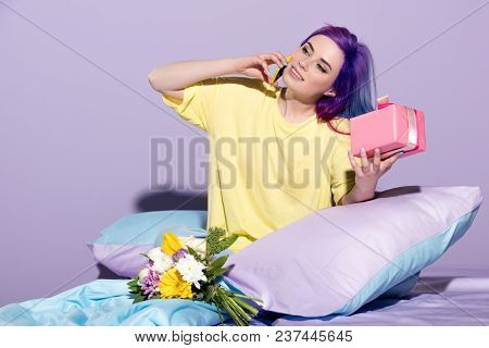 Happy Young Woman With Gift Box And Flowers Sitting In Bed And Talking By Phone