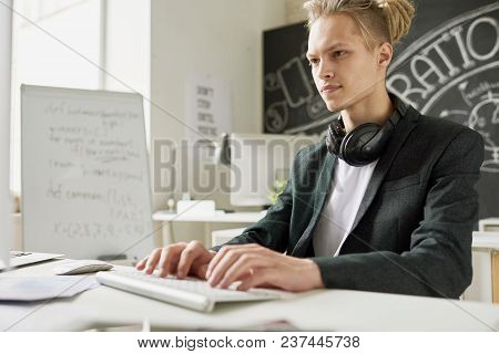 Serious Concentrated Handsome Young Male Mobile App Developer With Headphones On Neck Typing On Comp