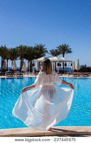 Luxurious Landscape With A Beautiful Caucasian Young Woman At The Swimming Pool At Resort Sharm El S
