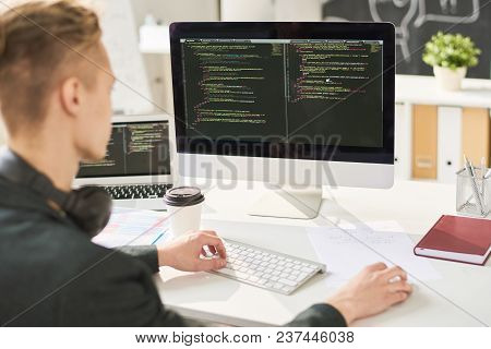 Busy Smart Web Developer Editing Computer Programming Code And Sitting At Table In Modern Office