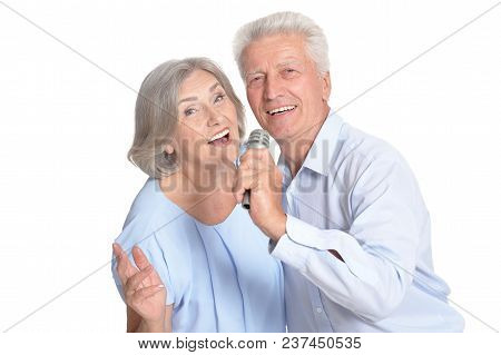 Senior Couple Singing Karaoke Isolated On White Background