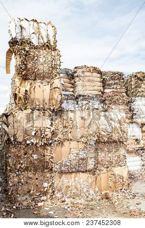 Pile Of Pressed Waste Paper Bales In The Yard.  Waste Paper Recycling.