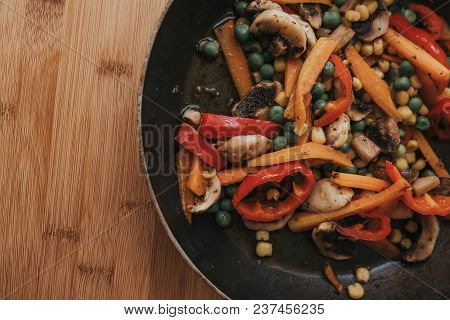 Delicious Vegetarian Food In A Pan, Vegetable Meal. Pea, Red Bell Pepper, , Carrots And Mushrooms In