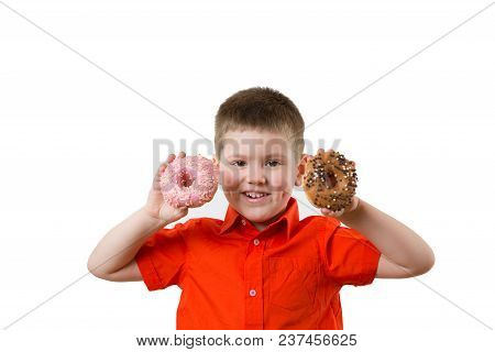Little Happy Cute Boy Is Eating Donut On Whte Background Wall. Child Is Having Fun With Donut. Tasty