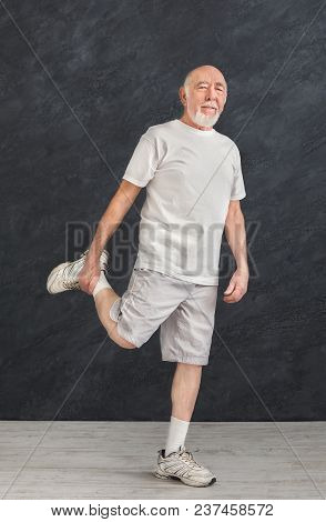 Senior Fitness Man Stretching His Legs Before Workout, Black Background. Active Lifestyle And Health
