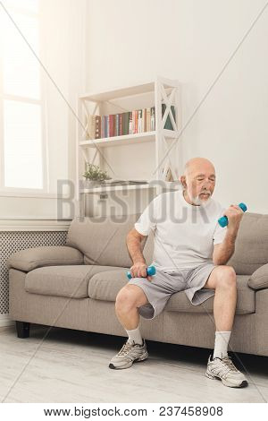 Senior Fitness Man Training With Dumbbells At Gym, Doing Strength Exercise For Biceps, Sitting On Co