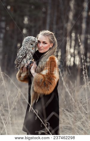 Woman Blond In Autumn In Fur Coat With Owl On Hand First Snow. Beautiful Girl With Long Hair In Natu