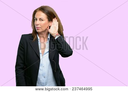Middle age business woman holding hand near ear trying to listen to interesting news expressing communication concept and gossip