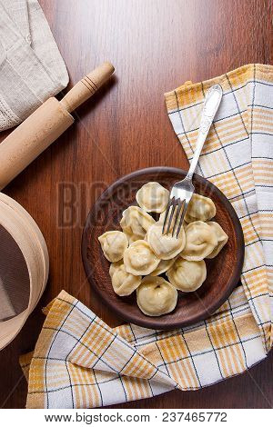 Served In Clay Plate Ukrainian Meat Dumplings Or Ravioli On Wooden Background..