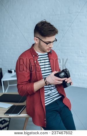 Young Bearded Man In Glasses Holding Camera By Working Table