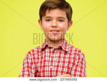 Handsome toddler child with green eyes with crossed arms confident and happy with a big natural smile laughing over yellow background