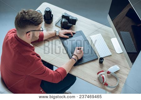 Young Bearded Man Using Graphic Tablet By Table With Computer