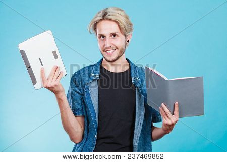 Male Student Holding Ebook Reader And Book. Choice Between Modern Educational Technology And Traditi