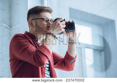 Man Freelancer At Work Shooting With Digital Camera