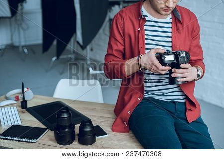 Young Bearded Man Holding Camera While Sitting On Working Table