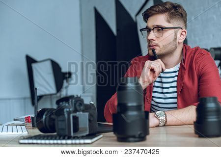 Thoughtful Freelancer Working By Table With Camera