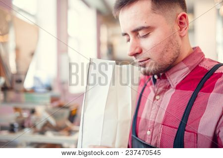 Picture of man sniffing coffee in paper bag