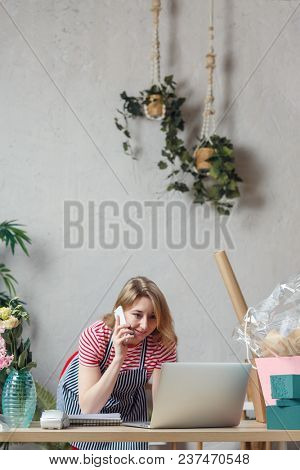 Photo of florist girl talking on phone in flower shop