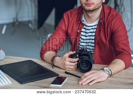 Young Bearded Man Holding Camera By Table With Computer