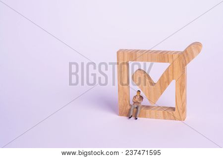 The Person Is Running For Election. A Man Is Sitting On A Wooden Checkbox, A Tick For Voting. The Co
