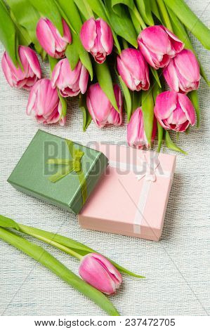Pink Tulip Bouquet And Small Gifts On Light Background,