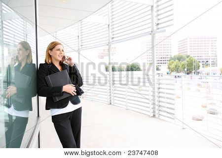 A pretty, young business woman at office building on phone