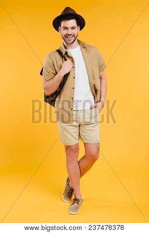 Full Length View Of Handsome Young Man In Shorts And Hat Holding Backpack And Smiling At Camera Isol