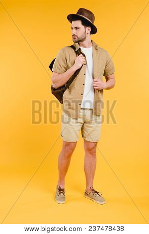 Full Length View Of Handsome Young Man In Shorts And Hat Holding Backpack And Looking Away Isolated
