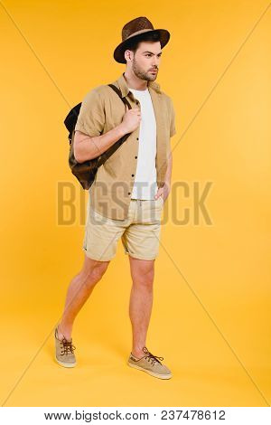 Full Length View Of Young Man In Shorts And Hat Holding Backpack And Walking Isolated On Yellow
