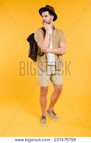 Full Length View Of Young Man In Shorts With Backpack Looking Away Isolated On Yellow