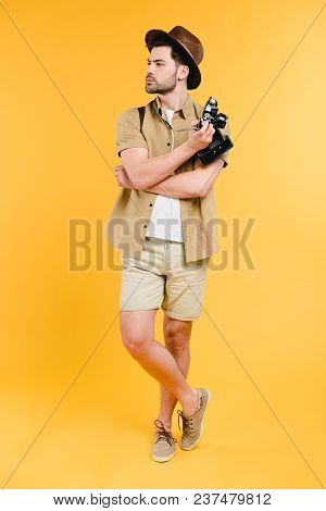 Full Length View Of Young Male Traveler Holding Camera And Looking Away Isolated On Yellow