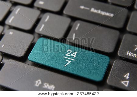 Online business always open internet concept: blue key button with 24/7 working hours symbol on laptop keyboard. poster