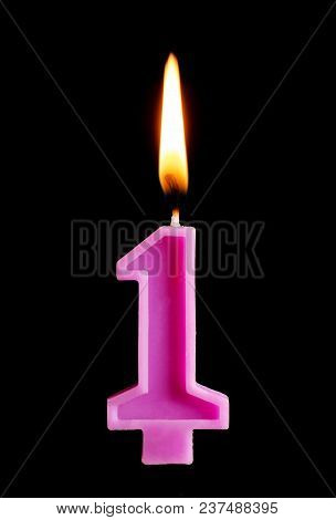 Burning Birthday Candle In The Form Of 1 One Figures For Cake Isolated On Black Background. The Conc