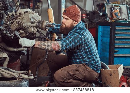 Brutal Tattooed Bearded Mechanic Specialist Repairs The Car Engine Which Is Raised On The Hydraulic