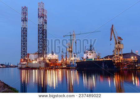 Oil Rig Docked In Shipyard Of Gdansk At Dusk. Poland