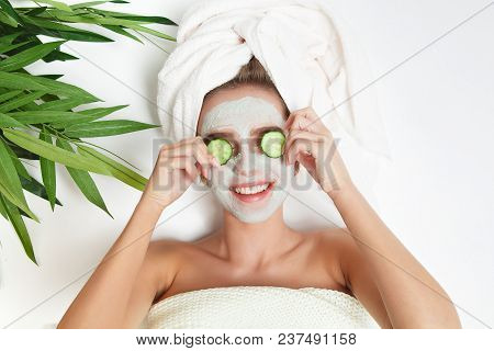 Portrait Of Beauty Woman Laying With Towel On The Head, Cucumber On Her Eyes, Facial Mask. Spa Thera