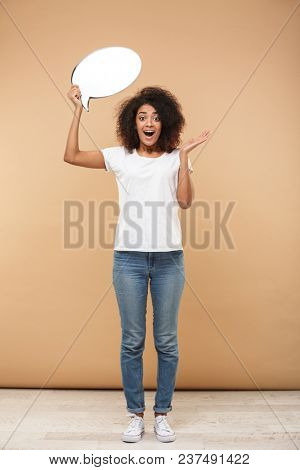 Full length portrait of an excited young african woman holding empty speech bubble isolated over beige background