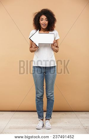 Full length portrait of a happy young african woman pointing away with an arrow isolated over beige background