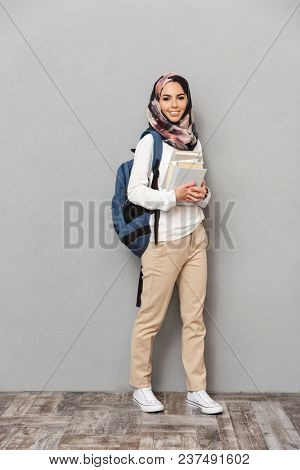 Full length portrait of a smiling young arabian woman student with backpack holding books isolated over gray background