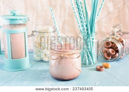 Cocoa In A Jar Of Straw. In The Background, A Blue Coffee Pot, Marshmallows And Turquoise Cocktail T